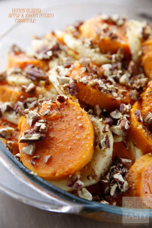 Close up of sliced baked sweet potatoes alternating with apple slices topped with chopped toasted pecans