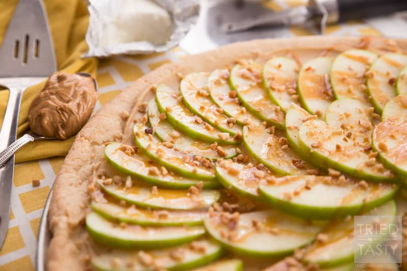 Taffy Apple Pizza // When you start with a sugar cookie crust, it's hard to go wrong. Add on a creamy layer of peanut butter and cream cheese. Top with sliced apples, caramel, and chopped nuts. This Taffy Apple Pizza will be the star of the party! | Tried and Tasty