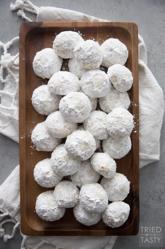 Stack of nut butterball cookies on a brown rectangular wooden plate resting on a dish towel