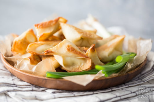 Plate of wontons with green onion garnish on a linen napkin