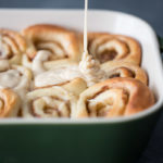 Close up shot of cinnamon rolls being drizzled with maple icing