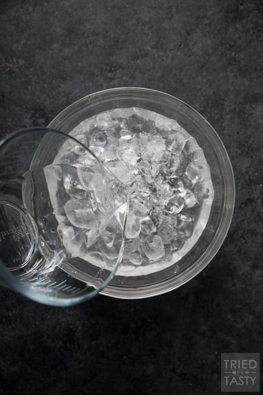 Water being poured into a glass bowl of ice