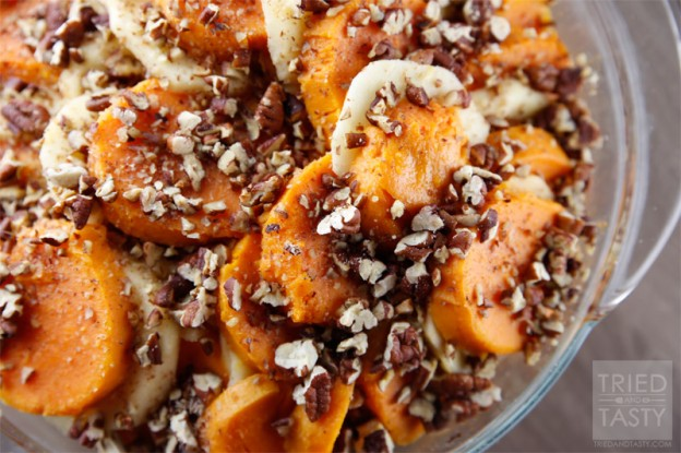 Close up shot of sliced sweet potatoes alternating with sliced apples topped with chopped toasted pecans in a glass bowl
