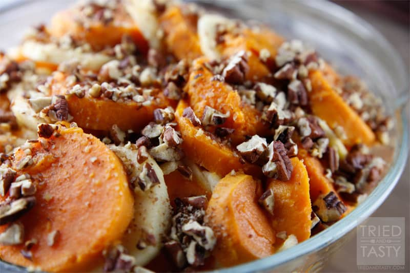 Close up image of sliced baked sweet potatoes alternating with apple slices topped with chopped toasted pecans in a baking dish