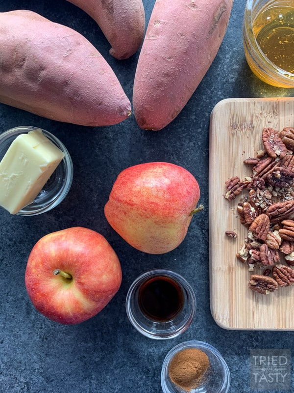 Three sweet potatoes, a bowl with butter, two gala apples, a pinch bowl of vanilla, roughly chopped pecans on a wooden cutting board & a small bowl of honey on a counter top