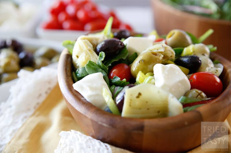 Mediterranean Salad With A Creamy Feta Dressing // The most wonderful Mediterranean Salad featuring the delicious flavors of marinated artichokes, fresh mozzarella, savory olives, and red onion. Finish it off with the most delectable creamy feta dressing for a knockout pairing! | Tried and Tasty