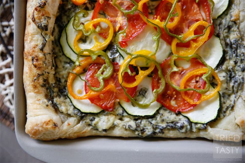 Spinach & Artichoke Veggie Pizza // A delicious way to use up some of your favorite seasonal vegetables. For the gardeners, you can grab most all of these veggies from your backyard. For the non-gardeners run to your nearest farmer's market & plan this pizza for your next get together! | Tried and Tasty