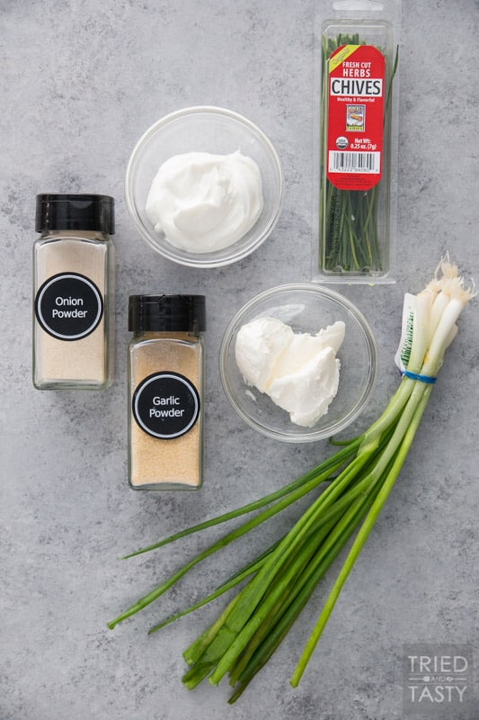 Spice jars with garlic powder, onion powder, a bowl of sour cream, a bowl of cream cheese, chives and green onions on a counter