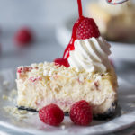 Raspberry sauce drizzled on a slice of Cheesecake Factory White Chocolate Raspberry Truffle Cheesecake on a white plate