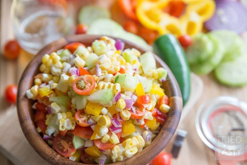 Fresh Sweet Corn Salad // Nothing screams summer like fresh corn! Am I right? I love fresh sweet corn all kinds of different ways, but I especially love it in this yummy salad. Jam packed with all kinds of bright fun veggies, coated in a tangy refined sugar-free dressing! Pefect for any potluck, BBQ, or picnic. | Tried and Tasty