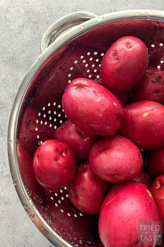 10 lbs of red potatoes in a silver colander