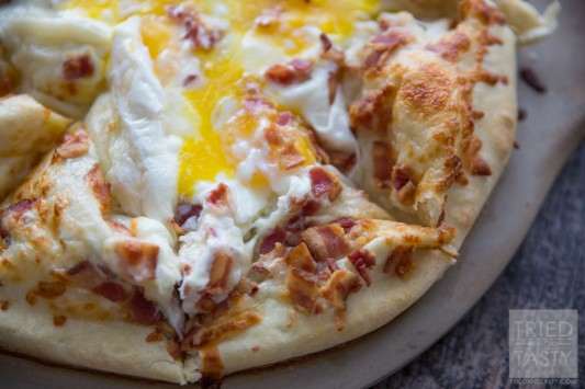 Breakfast Pizza // Make breakfast fun with this delicious pizza! Eggs, bacon and cheese + a crust is all you need. Great the morning of and also still tasty as leftovers!   Tried and Tasty