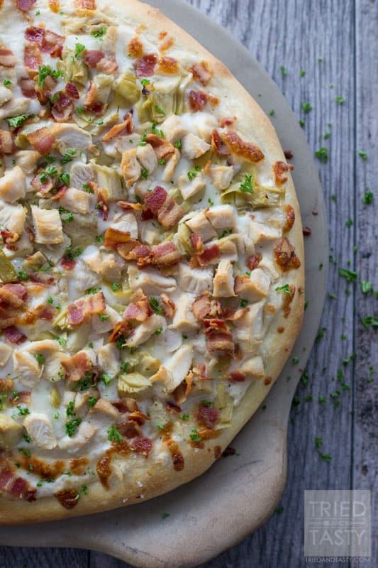 Chicken Bacon Artichoke Alfredo Pizza // One of the best pizza combinations out there. Super simple to throw together, but packed with great flavor. Prepare a delicious crust and top with the best of the best. This pizza makes for a great lunch or dinner - and even delicious as leftovers! | Tried and Tasty