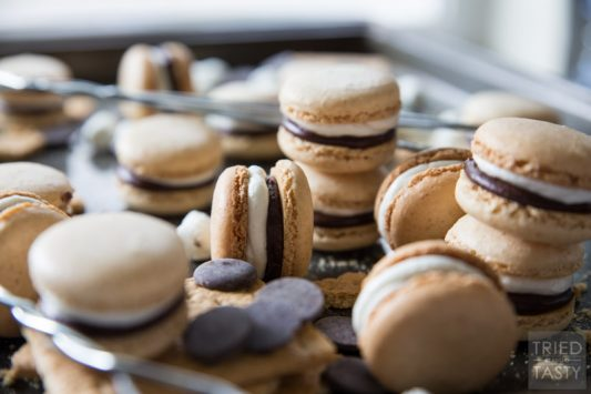 S'mores French Macarons // Whether it's National S'mores Day or not, these french macarons are the PERFECT way to celebrate anytime! With a tasty graham macaron, marshmallow buttercream, and chocolate ganache - these little babies will be devoured by everyone! | Tried and Tasty