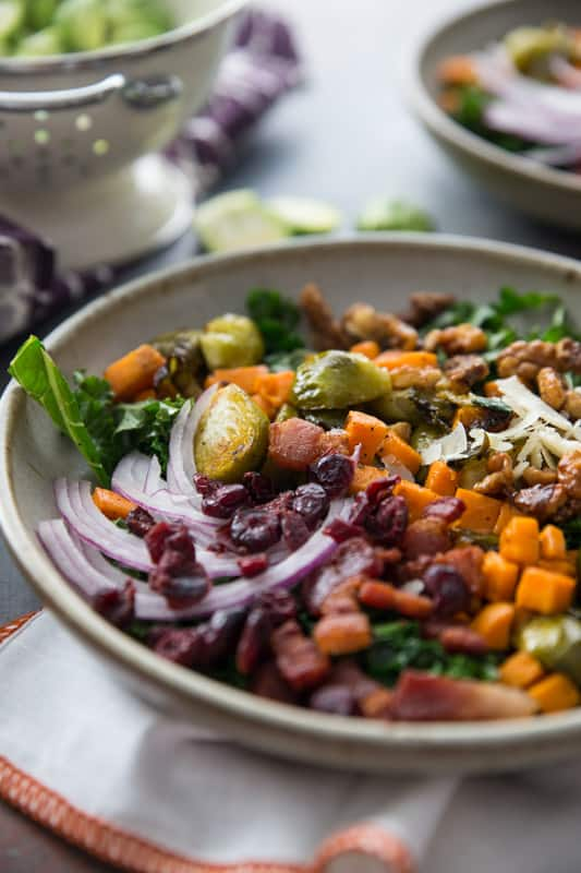 Sweet Potato, Kale and Brussels Sprouts Winter Bowl // This winter bowl is the perfect cure to the seasonal blues. Packed with delicious veggies and ever so slightly sweetened with maple candied walnuts and cranberries! | Tried and Tasty