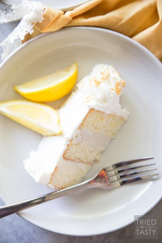 Lemon Lovers Ice Cream Cake // Calling all lemon lovers, this ice cream cake screams summer with the most delicious lemon cake sandwiched between a layer of lemon ice cream and a layer of vanilla bean ice cream covered in light and fluffy lemon whipped cream frosting! | Tried and Tasty