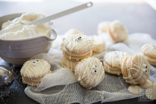 Mummy Macs {Vanilla Bean French Macarons} // Be the hit of your holiday party with these adorable mummy french macarons. Made with a classic vanilla bean cookie sandwiched together by the most delicious light & fluffy vanilla bean buttercream frosting! | Tried and Tasty