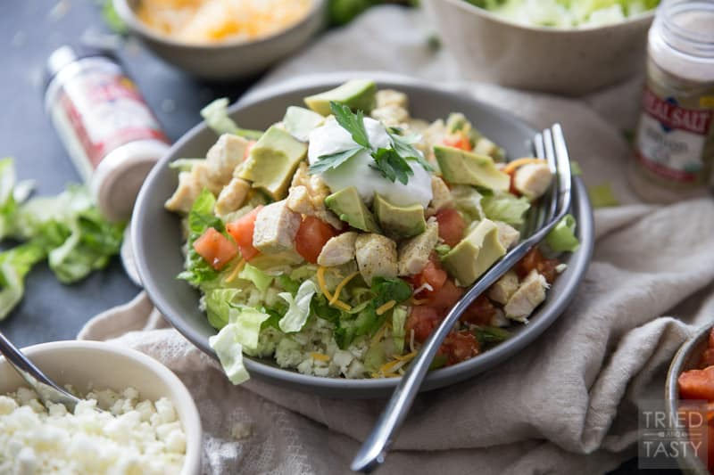 Skinny Burrito Bowl | This just might be the healthiest, most guilt free burrito bowl that you've ever seen! It's built on a fluffy bed of cauliflower rice and topped with traditional favorites like cheese and diced avocado. | Tried and Tasty