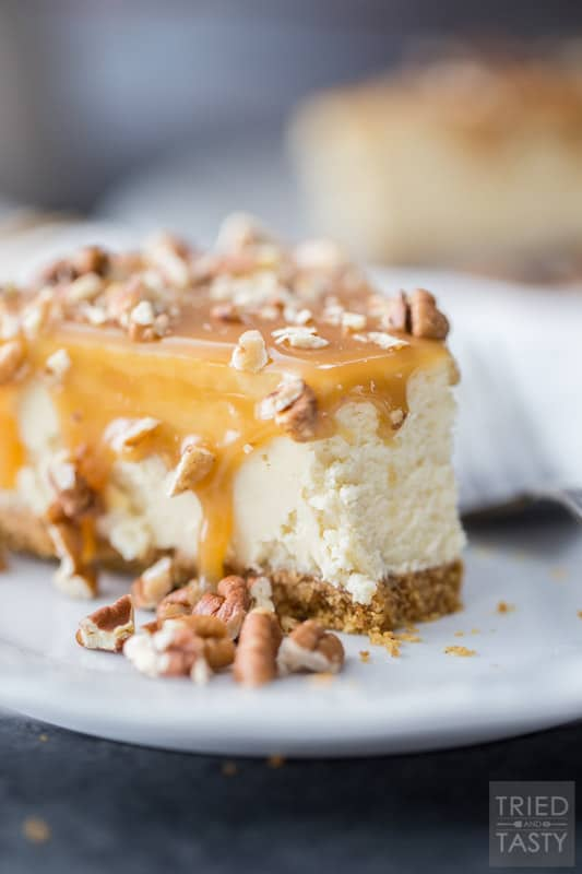 Slice of cheesecake covered in caramel & topped with pecans on a white plate with silver fork
