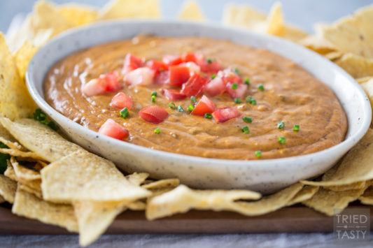 Bowl of queso in a ceramic dish surrounded by tortilla chips and topped with chopped tomato and diced chives