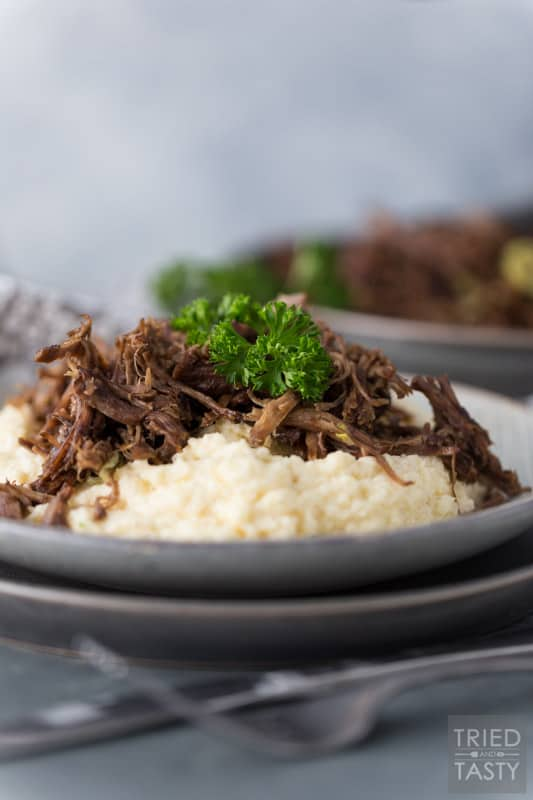 Two plates stacked with mashed cauliflower topped with shredded pot roast garnished with parsley