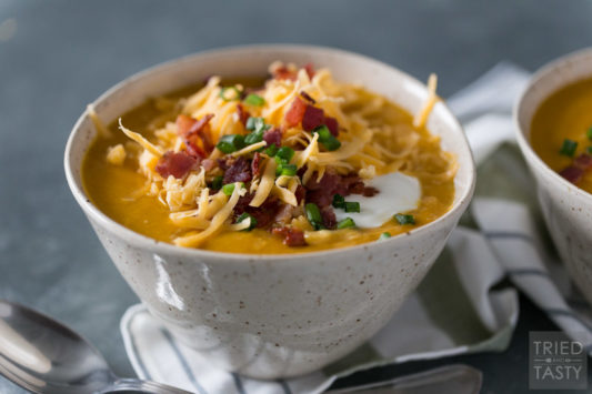 Sweet potato soup in a ceramic bowl topped with shredded cheddar, bacon, sour cream & scallions