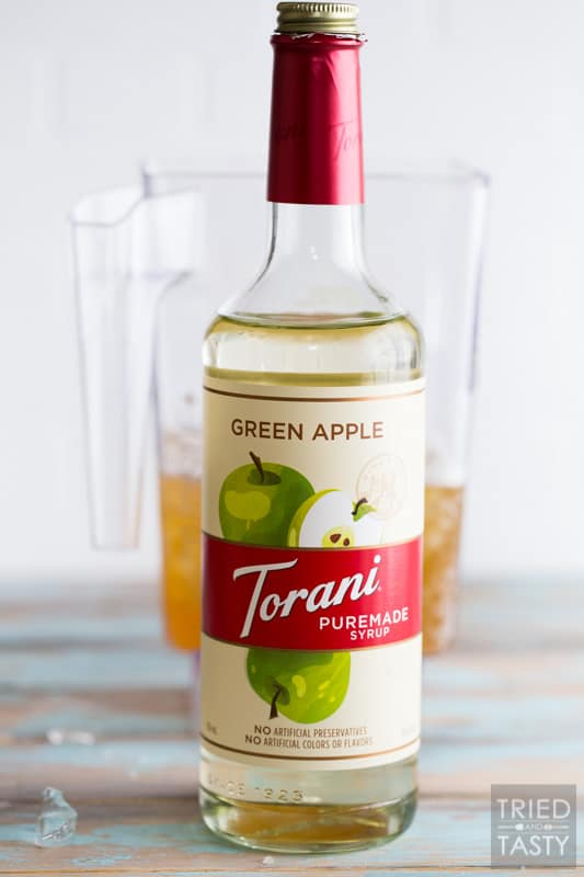 Torani Green Apple Puremade Syrup with Blender jar filled with Kombucha in the background.