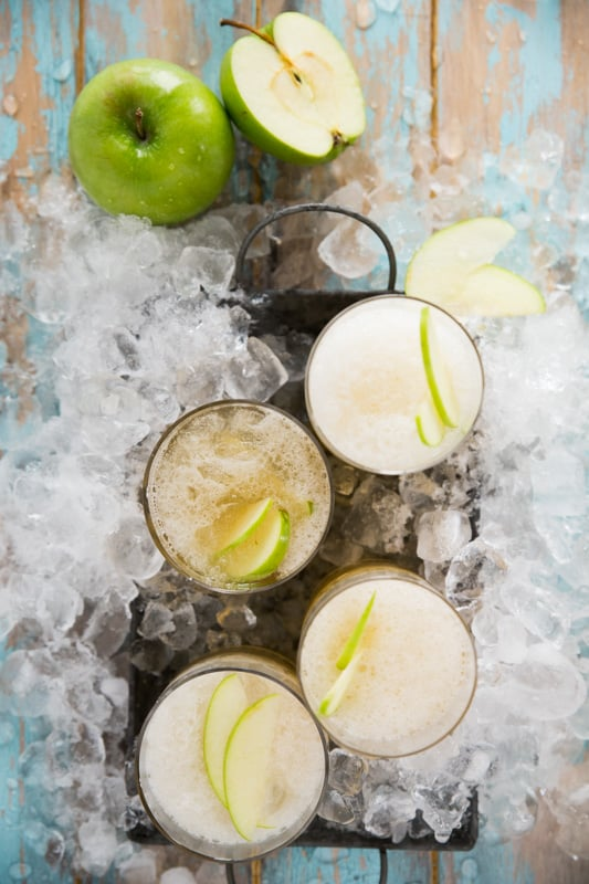 Several glasses of Green Apple Kombucha Slushy, with green apples and ice in the background.