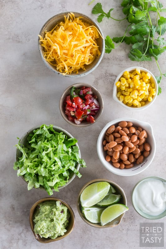 Ingredients used to garnish barbacoa beef burrito bowls: cheese, salsa, corn, lettuce, pinto beans, gaucamole, lime, cilantro & sour cream