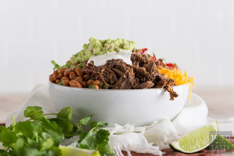Barbacoa Beef Burrito Bowl with cheese, salsa, corn, lettuce, pinto beans, gaucamole, lime, cilantro & sour cream on top.