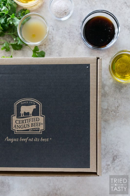 A cardboard box with the Certified Angus Beef ® brand logo on it. Marinade ingredients surround the box.
