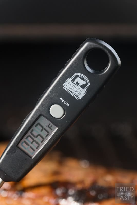 A digital meat thermometer showing the temperature of the steak on the grill. In this case, 135.3 degrees F.