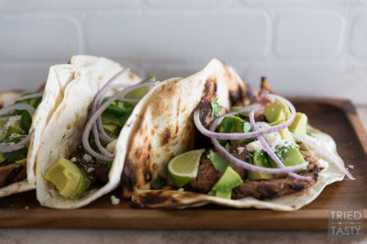 A side angle showing steak tacos on a cutting board.
