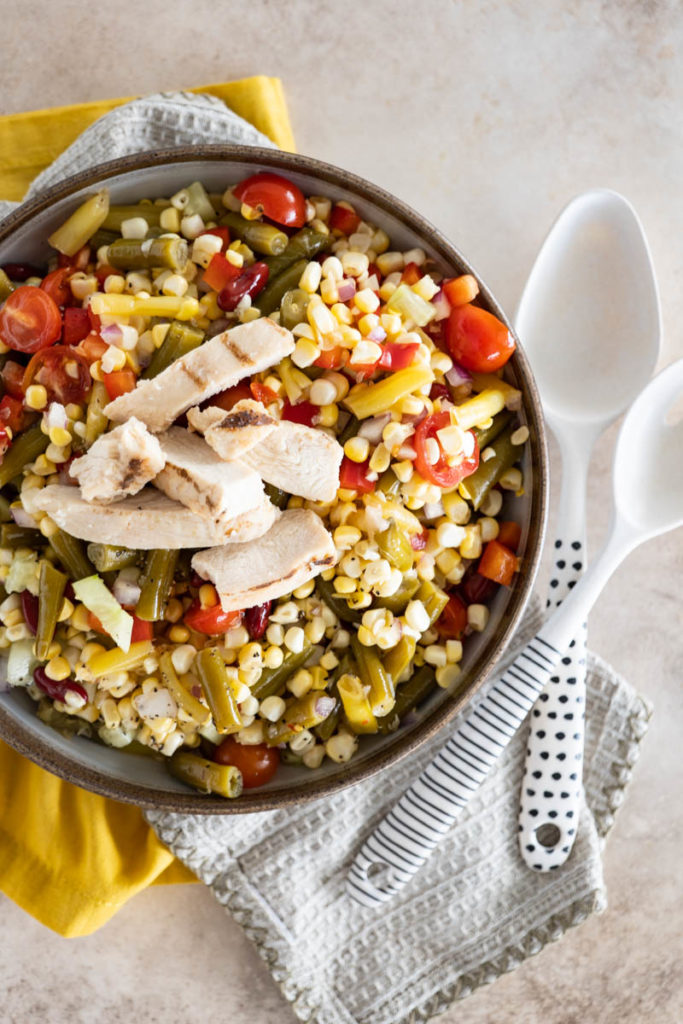 A prepared bowl of bean salad, topped with sliced grilled chicken breast.