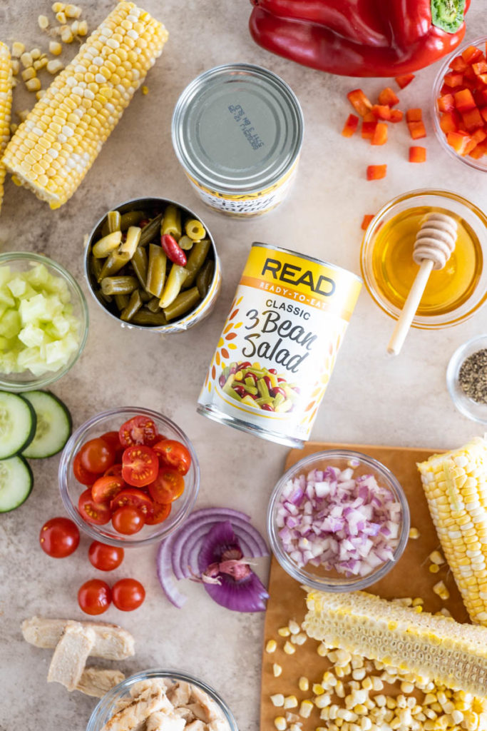A photo of the various ingredients used in this recipe, including a can of READ 3 Bean Salad, Cherry Tomatoes, Red Onion, Corn on the Cob, Cucumber, Honey, and Chicken Breast.