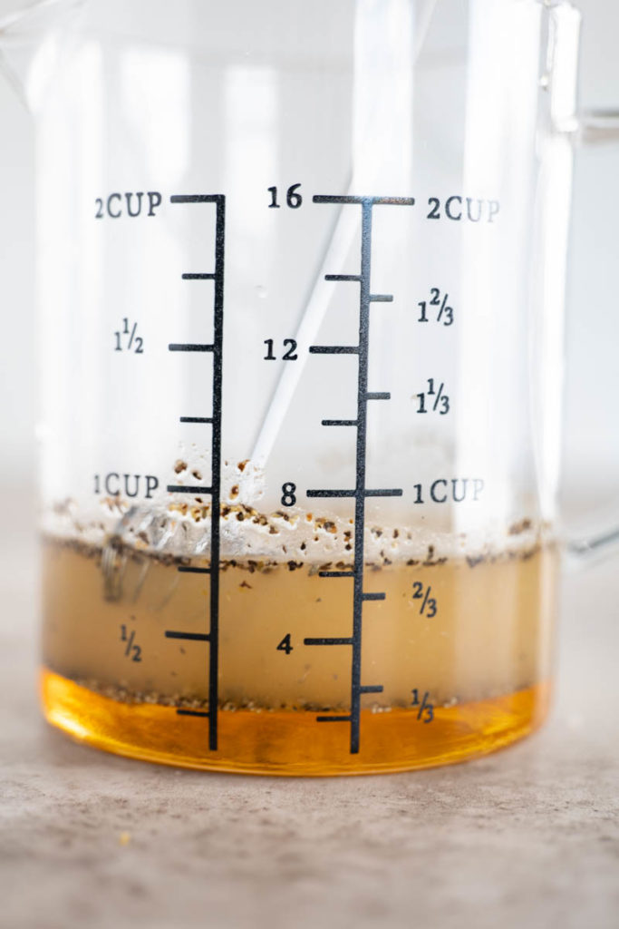 A glass measuring cup containing salad dressing with spices.